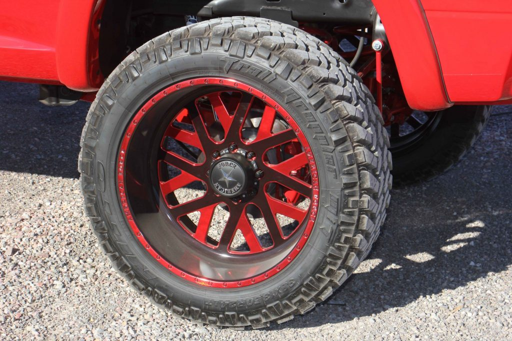 Rolling stock is a set of American Force 24x12 inch Whiskey SF8s with a custom red finish, wrapped in 38-inch tall Nitto Trail Grapplers.