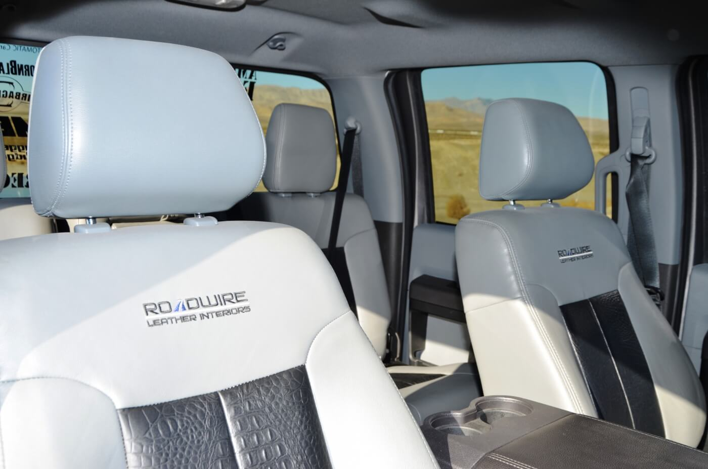 The interior features a mass of stereo upgrades from Pioneer and PowerBass as well as multiple monitors for passenger TV viewing. The seats were wrapped in custom two-tone leather for the utmost in road trip comfort.