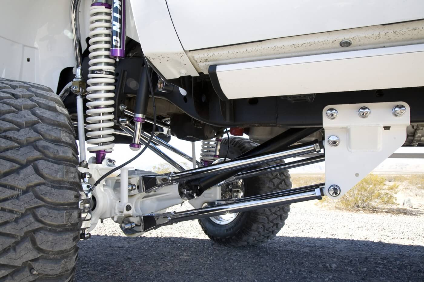 The back half of the front suspensions can be seen here. Notice that frame brackets have been painted white, while the upper and lower control arms are chrome plated. Look closely and you can also see the Amp Research steps that have been painted white to match the truck.