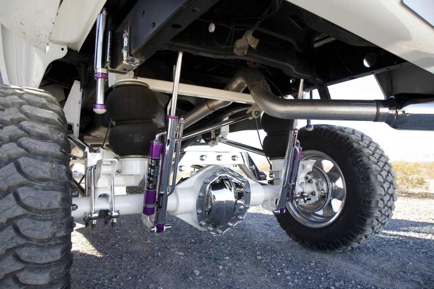 Here you see the rear shocks also from King. These are attached remote-reservoir units that work with the air bag rear suspension. Notice the chrome rear diff cover and brake backing plates. The axle is the original AAM 10.5 but it was powder coated white to match the body. Smith went show-quality all the way on this built.