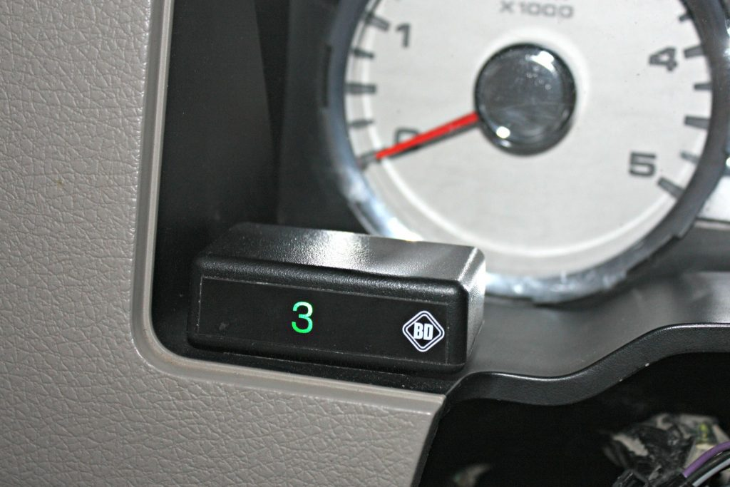9. The Tapshifter kit includes this handy little display to show drivers which gear has been selected while in the manual shift mode. The module will display gears 1-5 as selected by the button on the shift lever. It can be placed within easy viewing right on the dash panel behind the steering wheel using the included double-sided Velcro tape (no drilling required).
