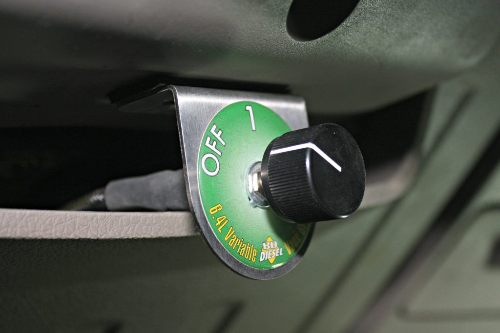 """11. The VVT system is controlled in-cab with a three-position switch that can be mounted just about anywhere the owner prefers. The small bracket offers endless mounting possibilities, but directly under the steering column offered the easiest reach without being in the way or requiring any drilling. Running the switch in """"off"""" allows the turbos to work like stock. Position One is Vane Control only for mild engine brake, while Position Two offers a Vane Control along with a more aggressive transmission downshift pattern to maximize engine braking."""