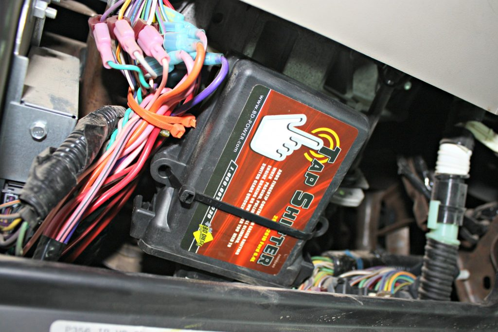 3. The Tap Shifter control box mounts under the dash and includes a professional-grade wiring harness to make the installation virtually plug and play. The kit will piggyback the factory OBD-II port and shift selector pigtail. There's one wire down along the frame that will need to be spliced and tapped into the BD module.