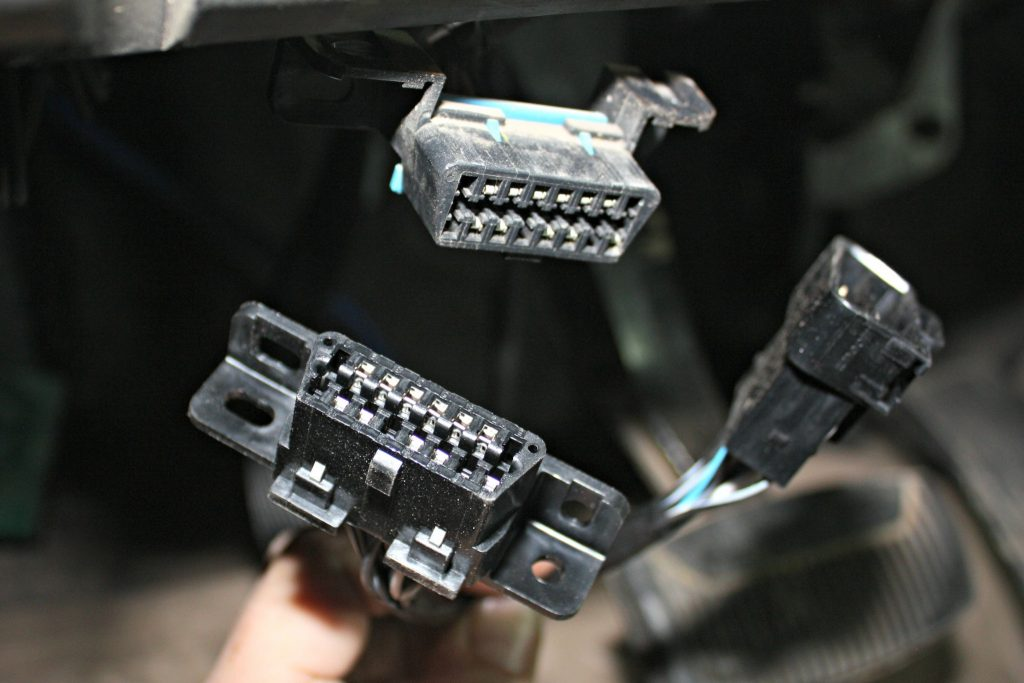 4. The factory OBD-II port will be removed from its mounting location under the dash and plugged into the female end of the OBD-II pigtail in the BD harness. The new male end of the harness will be fastened to the stock location under the dash.