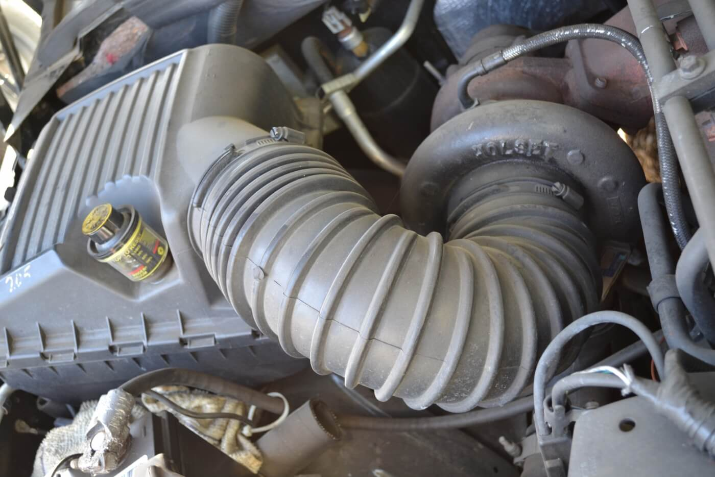 1. Our factory airbox, although functional, wasn't much to look at and had seen plenty of miles. The previous owner had used the space between the intake and battery box for storage, and below the white rag in the picture, we found a pair of vice grips, three more rags, and a spare coolant hose.