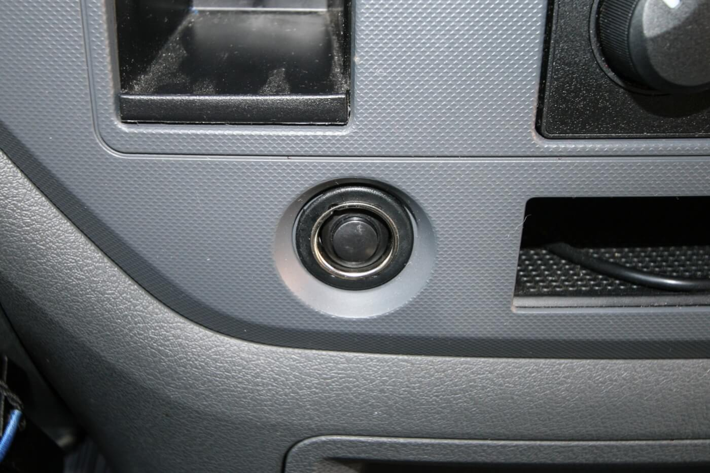 18. Since Daniel, the owner of the 2500 Dodge, had two cigarette lighter plugs, he decided to sacrifice one for a hidden air horn button. The included button fit nicely in the hole and some quick modifications to the OEM cigarette lighter meant, with the cap on, nobody knew that nearly 160 decibels of train horn were lurking underneath.