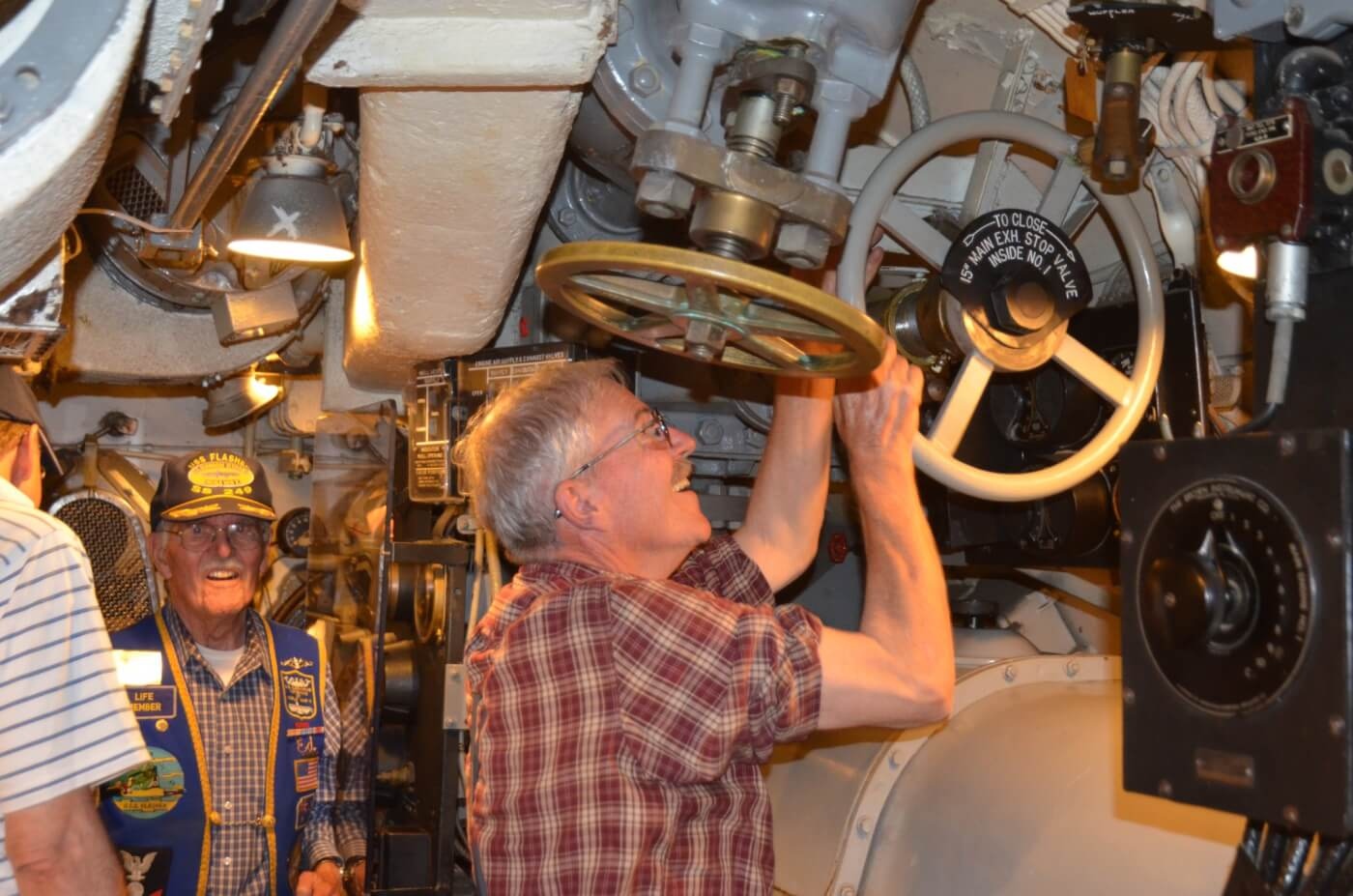 Charles Butcher, Chief of the Boat, opening the exhaust valve prior to starting the motor