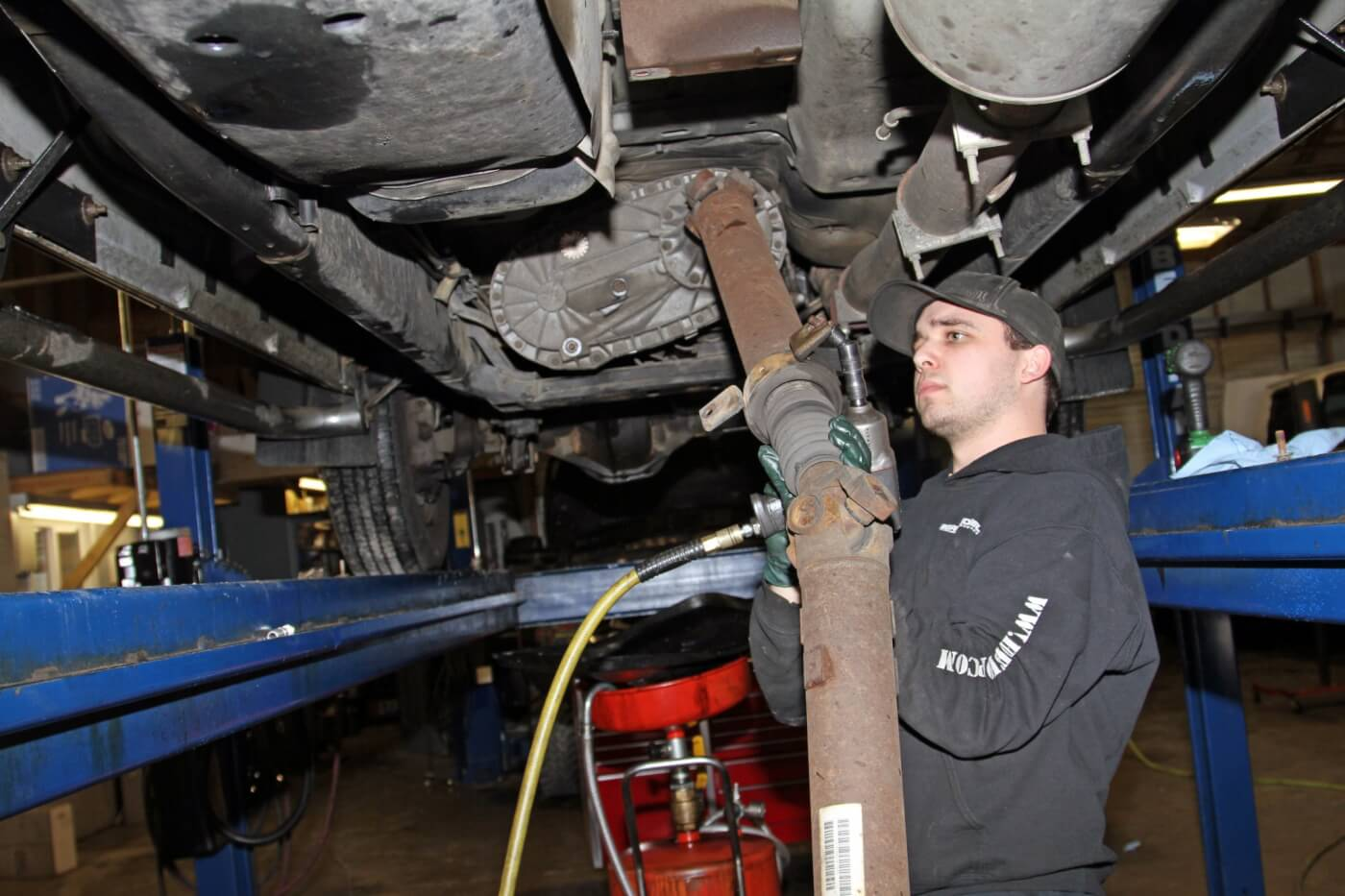 3. Then, he unbolted the rear drive shaft from the rear axle and carrier-bearing mount before removing the drive shaft.