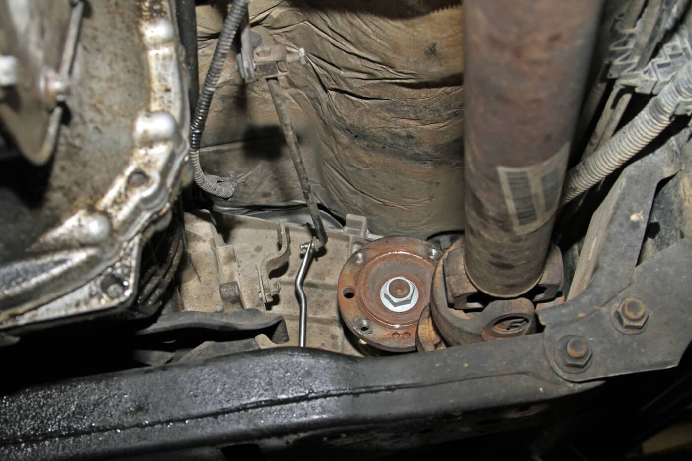 4. On the front side of the transfer case, Meraz unbolted the front drive shaft and secured it to the frame with a bungee cord; then he removed the linkage from the transfer case.