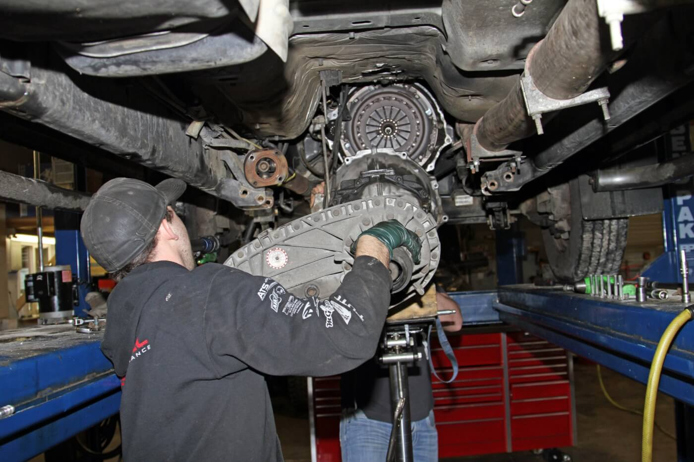 7. With the transmission secure, Meraz removed the bell housing bolts with an impact gun and the long extension with a wobble-socket to allow him to work at an angle and reach all of the mounting bolts. Then, the transmission assembly could be moved back to disengage the input shaft from the clutch and then lowered out of the way.