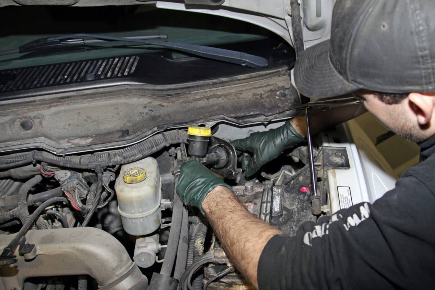 20. After lowering the truck, Meraz crawls under the dash to disconnect and unbolt the clutch master cylinder from the pedal and firewall. Then, he is able to pull the old hydraulic assembly out of the engine bay.