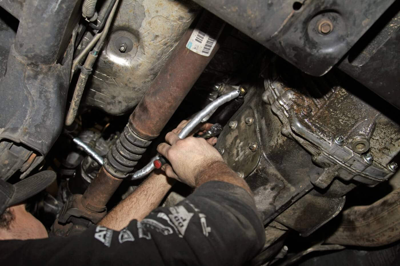 24. Climbing under the truck one more time, Meraz installed the slave cylinder on the transmission in the same way the old slave mounted.