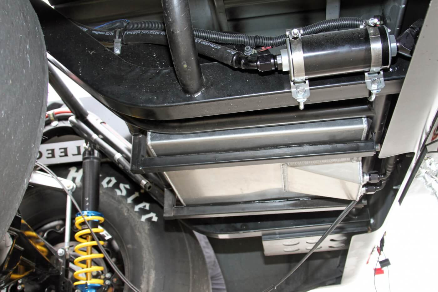 Crawling under the rear of the truck, you'll see the aluminum fuel cell securely mounted between the new frame rails. You can also see the Fuelab electric pump on the outside of the driver side rail and the battery mount on the outside of the passenger side rail.