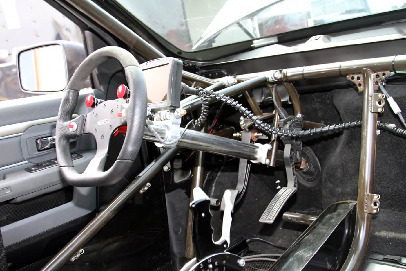 The roll cage provides a solid anchor point for the steering column and pedal assemblies. Milliken has a great view of the engine vitals with the Bosch Motorsport Display mounted in front of the Sparco steering wheel.