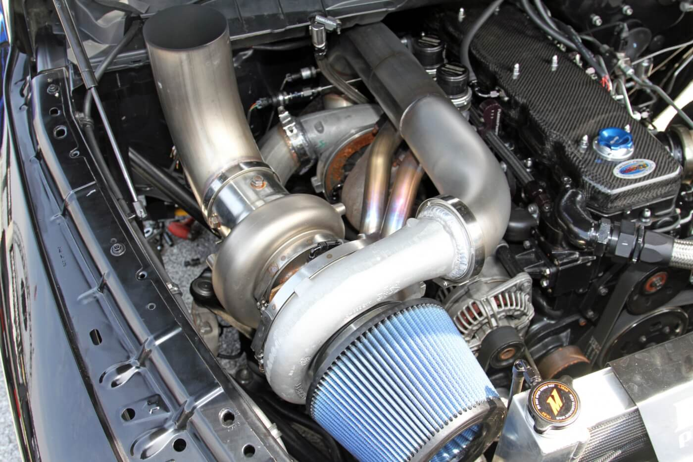 A large Garrett turbo is the primary, while a large Fleece Performance Engineering turbo is tucked under the Steed Speed manifold and custom stainless steel piping.