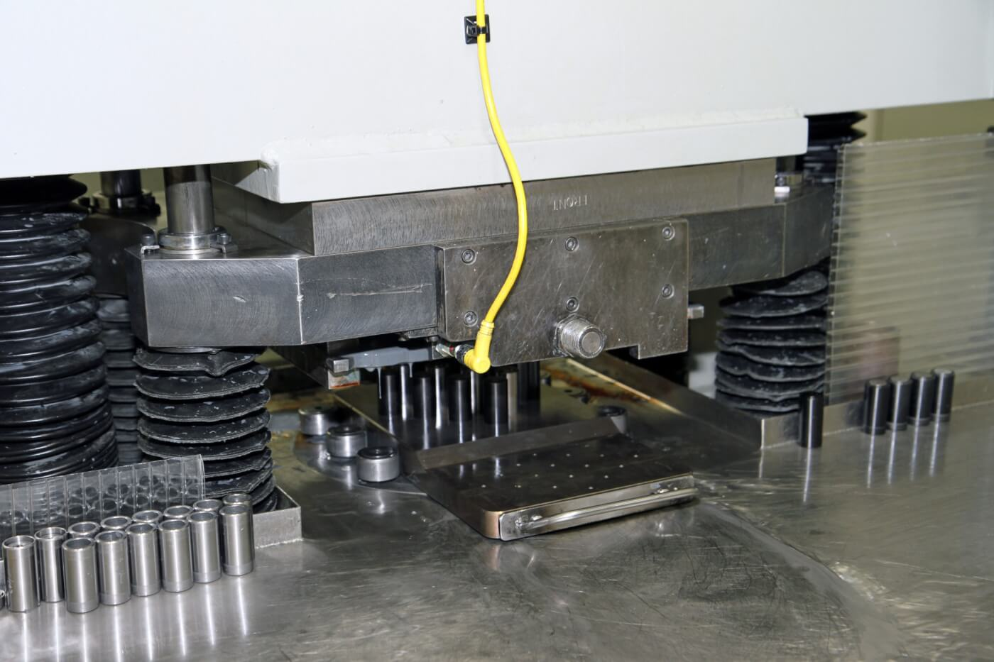 9. The fixture and nozzles are slid under the press where the abrasive media is forced through the nozzles under a great deal of pressure to enlarge and smooth the path of fuel flow through the nozzle.