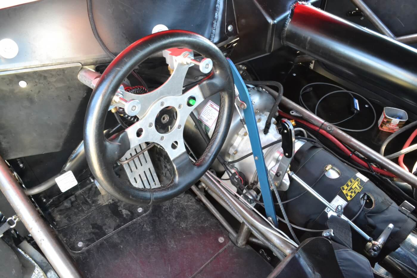 The interior is all business, with a carbon dash, minimal interior and tubular steering column. The black cover for the transmission is a transmission blanket, which protects the driver from any flying parts should breakage occur.
