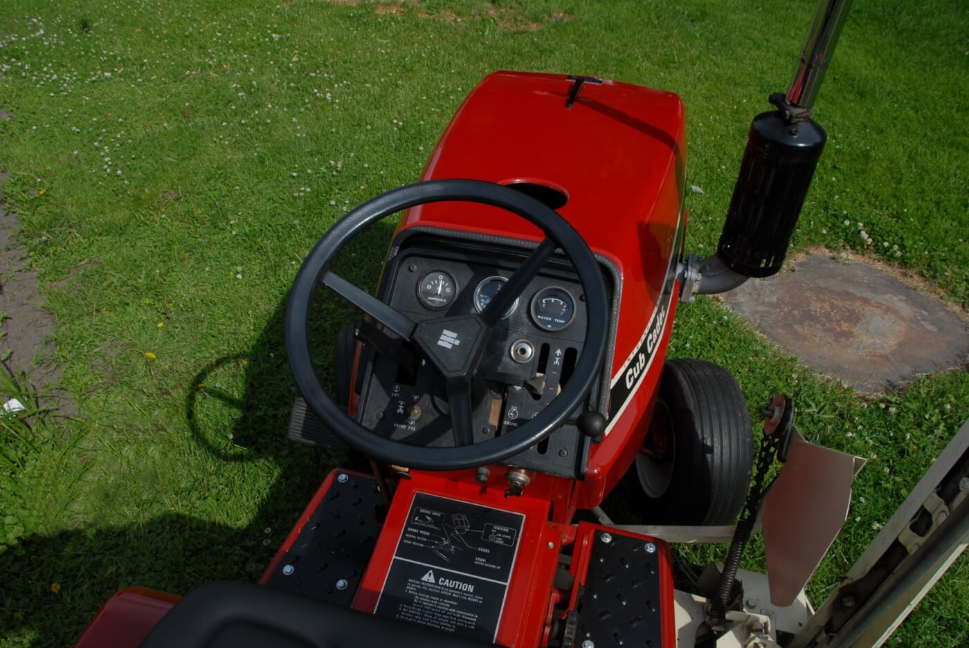 The 782D differs from most lawn tractors its size in having water temp and oil pressure gauges as well as a radiator and a fan. The Kubota diesel has a glow system, albeit an old school one, with a fourth glow plug mounted in the dash and observed through a sight hole just to the right of the steering column. The other controls are largely the same as the other 782s, and the fuel tank is located under the seat.