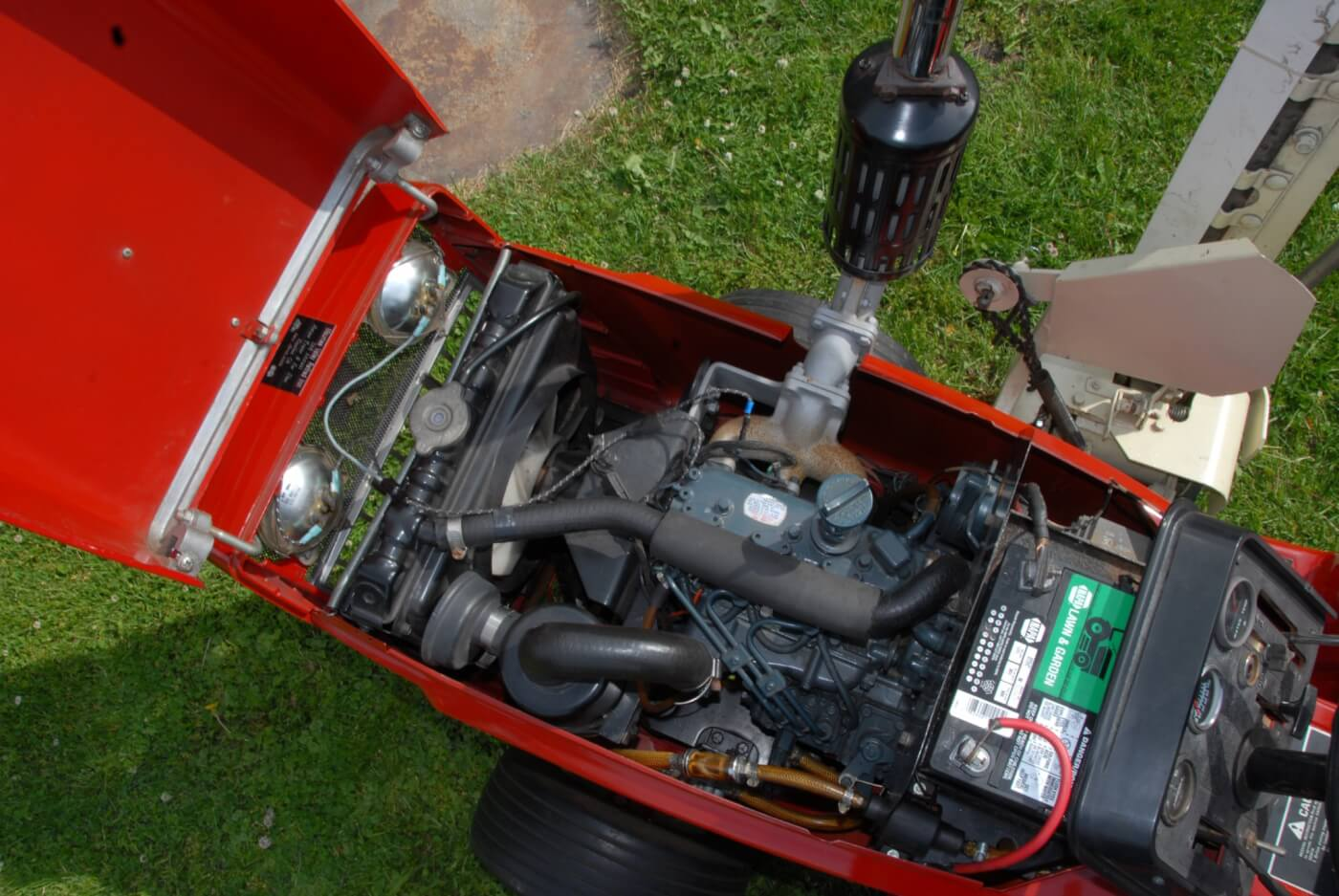 It's small, but it's a real diesel! The water cooled Kubota D-600B is a tiny three-cylinder natural-aspirated indirect-injected engine that can make up to 15 intermittent horsepower at 3,600 rpm. It displaces almost 37 cubic inches and uses a Bosch MD mini-pump with Bosch throttle type injectors that open at 1,991 psi. The pump is fed at 7 psi from a 4-gallon tank via an electric pump. The crankshaft is supported by four main bearings and the cylinders are dry sleeved in the iron block. The engine assembly, including the radiator and fan, weighs 136 lbs. The only downside to the installation is that the lawn and garden-sized battery may not always be up to spinning the 23:1 CR diesel in cold weather; a block heater was optional and probably necessary when using the 782D for winter work.