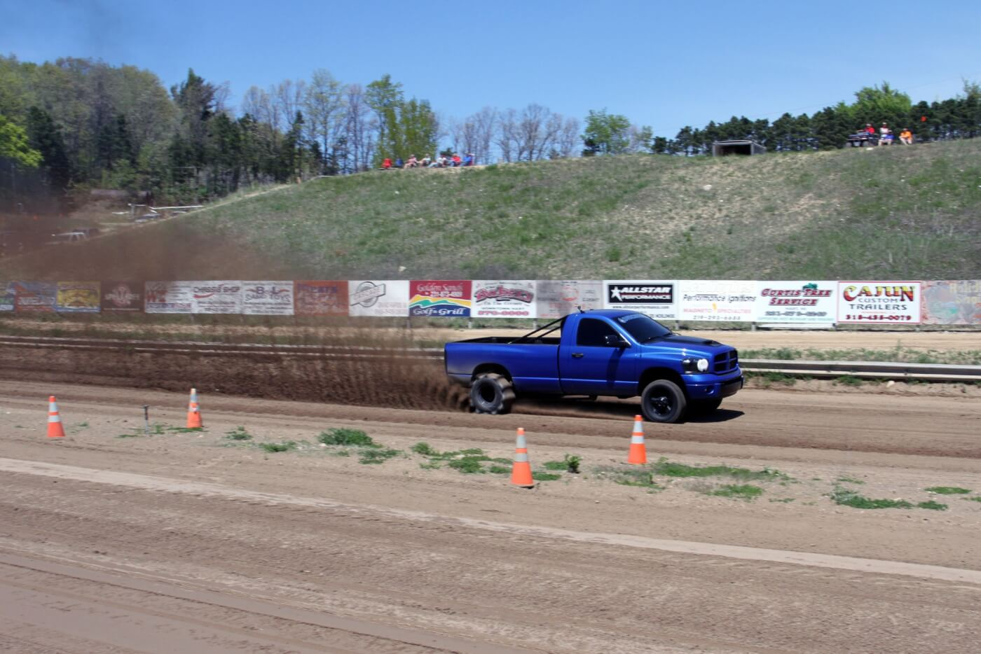 With the paddle tires mounted on the rear of the truck it throws up one heck of a rooster tail as it flies down the sand drag track on the way to the win.
