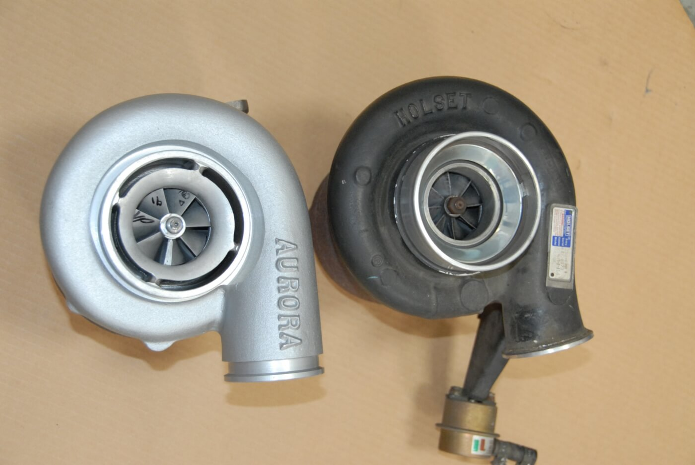 2. This close-up shows the differences between the Aurora 2000 turbo, next to the stock Holset unit. Besides the lack of a wastegate, note the larger discharge outlet on the Aurora, and slightly different exit angle, which allows air to exit more quickly from the compressor wheel. In addition, there's an inducer or bleed ring (the gap at the perimeter) to enhance the width of the boost map. And the compressor vanes have extended tips and a steeper pitch.