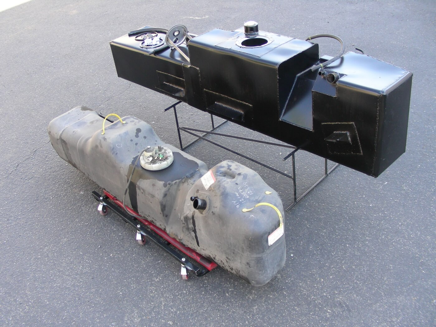 2. Note the dramatic difference in size between the factory unit and Aero's black steel tank. A custom-fabricated recess (right) was added to clear the gear splitter. All the necessary hardware and hoses are included, and rather than using straps that can rust over time, sturdy steel mounting tabs on the sides on the tank are through-bolted to the vehicle frame.