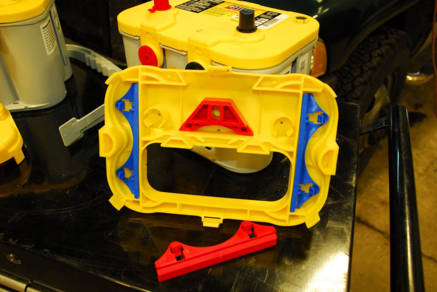 2. Inside the spacer/case are plastic adaptors that are designed to replace the factory bolt-down base clamps. They provide increased clamping force to secure the battery in place and are made to fit the unique shape of the Optima battery case.