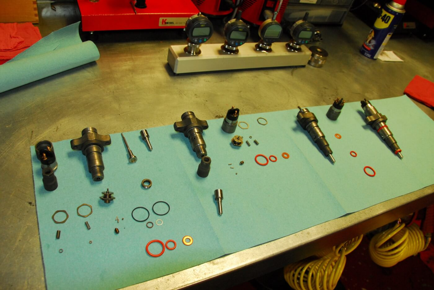 5. Shown here are all the high-pressure parts of a common rail system. These injectors are in various states of assembly. On the far left (top) are the solenoid, along with an air gap shim, armature, valve set with ball seat, seals and nozzle.