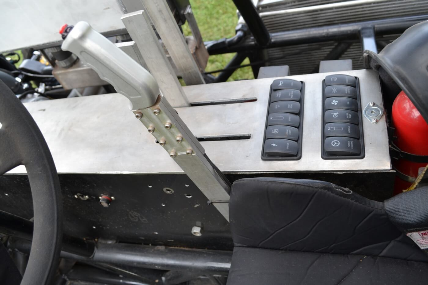The interior of the puller is sparse and functional. The lever to the right of the steering wheel is a hand throttle, which allows very precise control of the engine, especially on rough tracks. The OEM-style buttons on the switch panel were custom made, so were control things like the lighting, ignition and fuel pump.