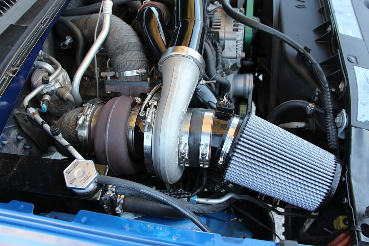 Kicking the passenger side battery out of its original location is this billet S480. It features the common 96mm turbine wheel, T6 flange, and 1.32 A/R turbine housing combination. In conjunction with the billet S366, the compound setup produces between 70-75 psi of boost on the street.