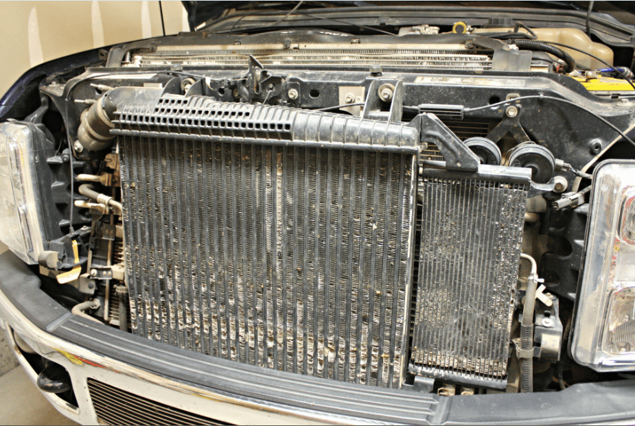 Hot-rodding a 2008-10 Power Stroke 6.4 puts heavy demands on the factory radiator and intercooler. We're replacing both on this 2008 Ford with components from Mishimoto. Installation begins by disconnecting the batteries and draining the coolant. We must remove several layers of coolers in order to get to the radiator.