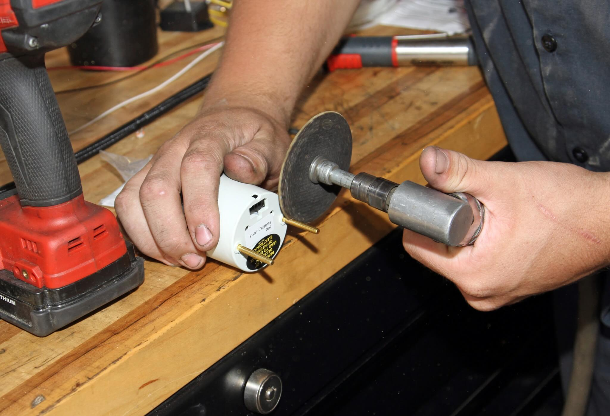6. Carter cuts off the mounting studs from the backside of the gauge to fit the HPOP gauge in the steering column pod.