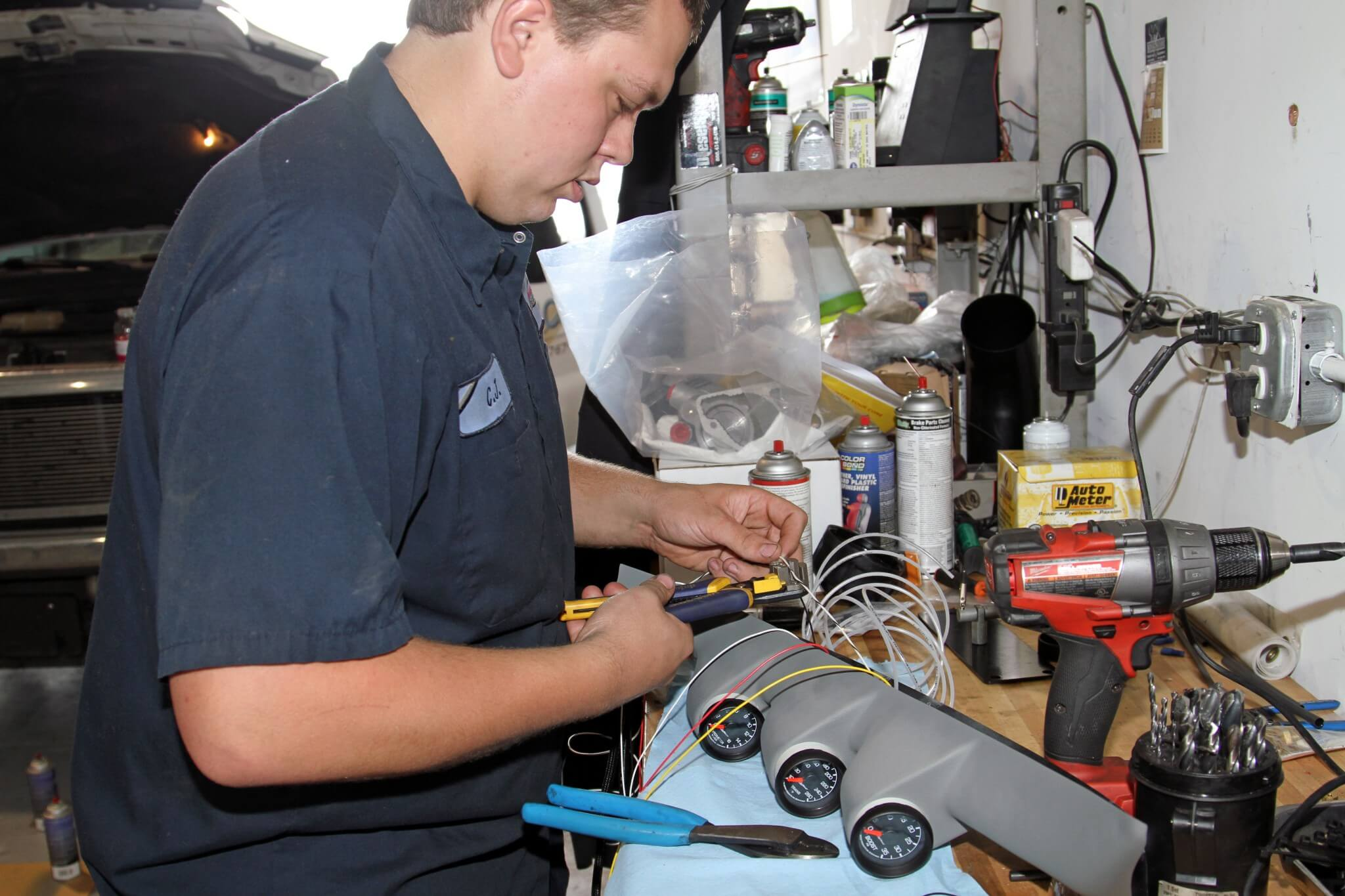 25. Carter slips the gauges partially into the pod and then wires the harnesses using solder and heat-shrink tubing for secure connections that will last the life of the truck.