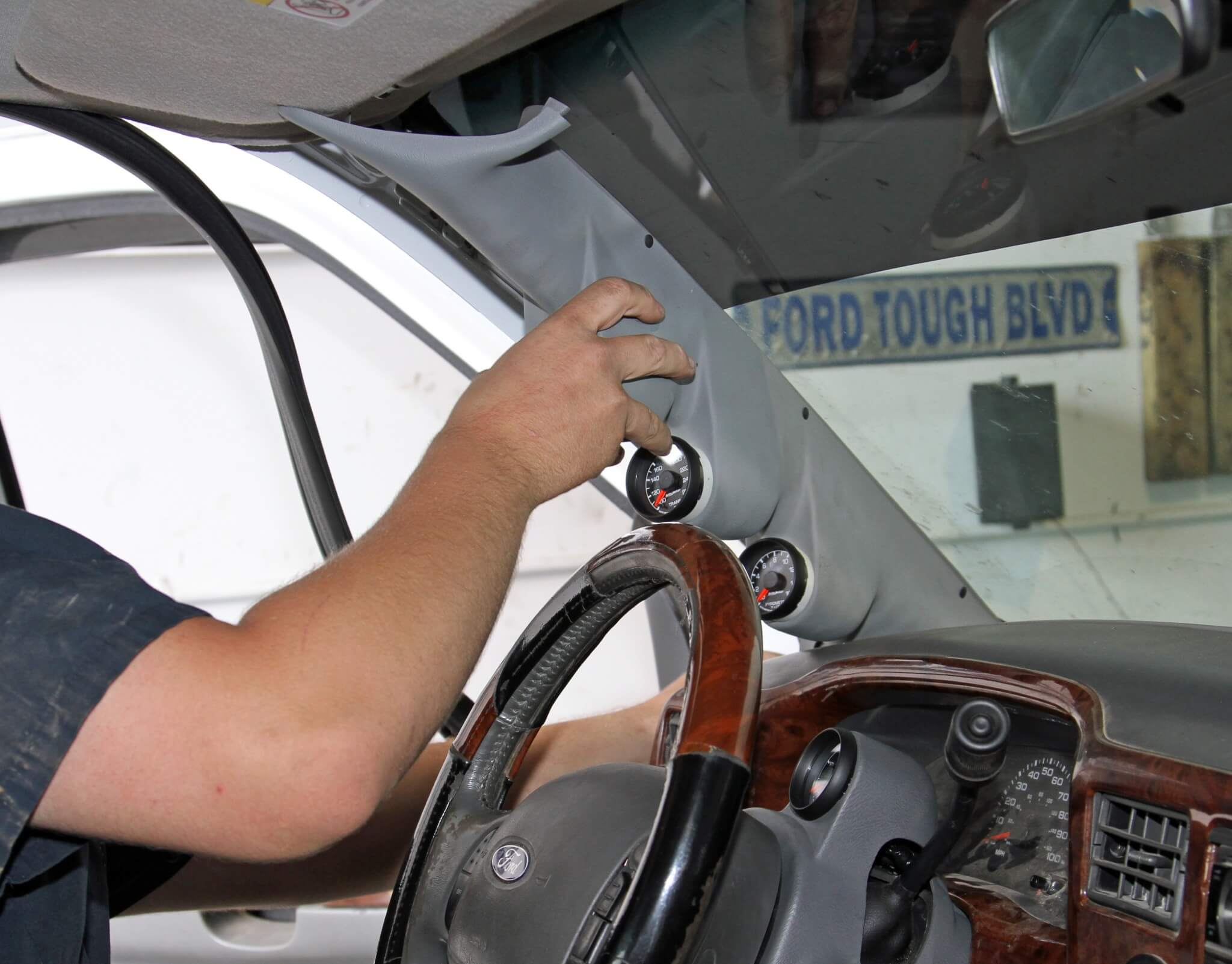 26. He then routes the harnesses through the A-pillar joint near the dash and installs the pod. He adjusts the angle of the gauges and presses them fully into the pod once it's installed to verify the angle from the driver's seat.