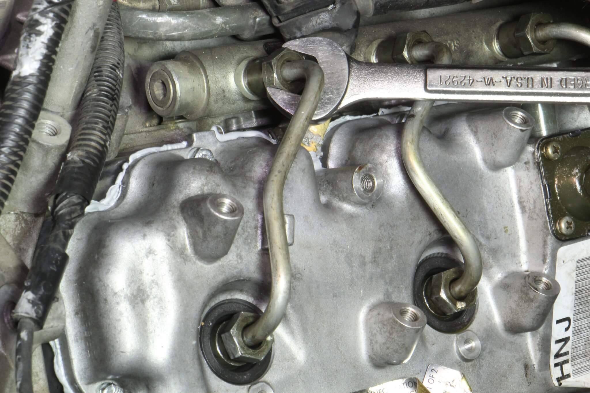 4. A 19mm open wrench was used to loosen the fuel injection lines from the fuel rail and fuel injectors. The upper fitting on the line is done first.