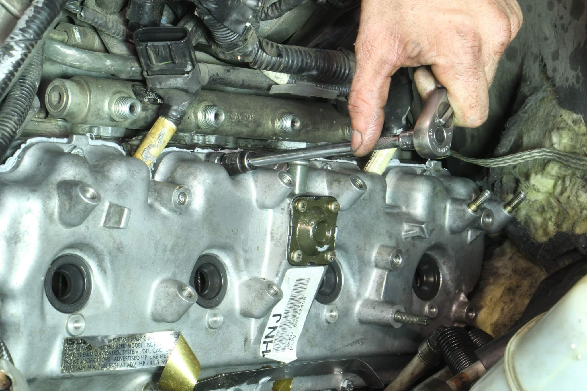20. After the silicone was given some time to cure, the top valve cover was then aligned and secured using a 10mm socket.