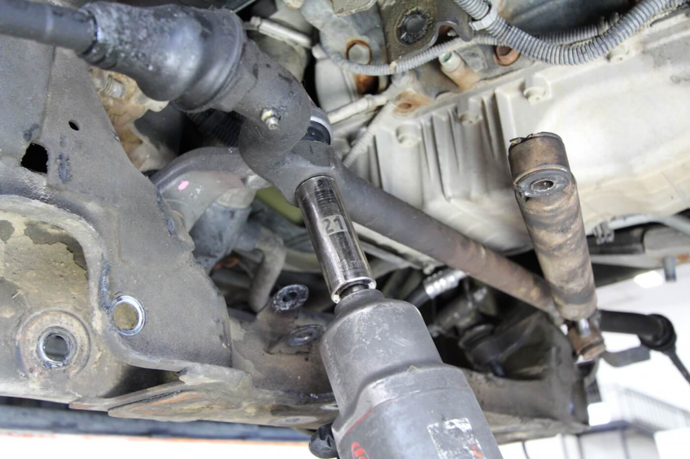 5. The IFS setup on the GM trucks has a center link that's connected to the pitman arm and idler arm. Here the link is being unbolted from the idler arm.