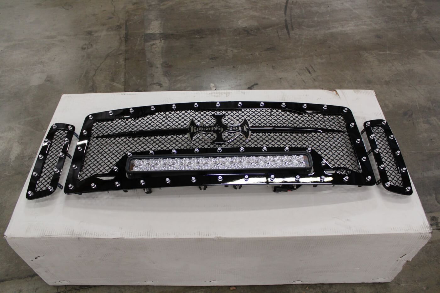 1. We decided to take a two-pronged approach to our truck's new nose. The first was the TrailReady bumper, installation of which was covered in our last issue (Diesel World, December 2014). The second is a Royalty Core RC1X Incredible LED grille. This three-piece insert includes a gloss black mesh grille surround with nickel-plated stud accents around all three pieces. The center portion includes a 22-in. Vision X LED light bar on adjustable mounts with an included wiring kit. The grille feels solid and well constructed, with TIG welding and stainless steel mounting hardware.