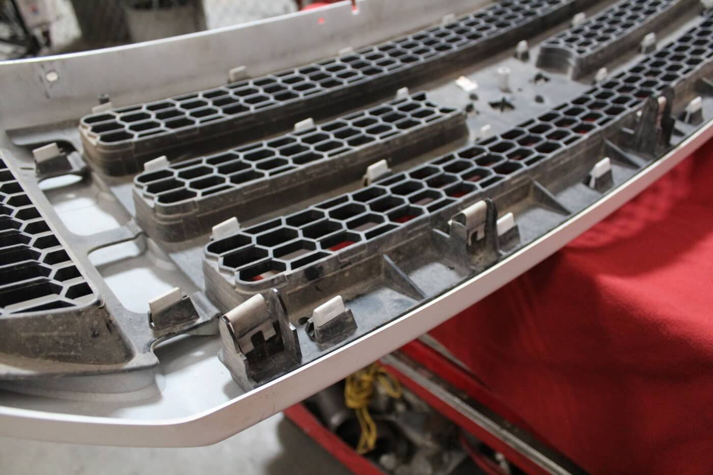"""3. Here's a closer look at the clips that hold the base of the grille in place. They're stubborn but they should pop out with a little pressure. Corder's method is to pull the upper portion of the grille out and then use a long pry bar behind the grille to """"help"""" the clips out of their homes in the core support."""