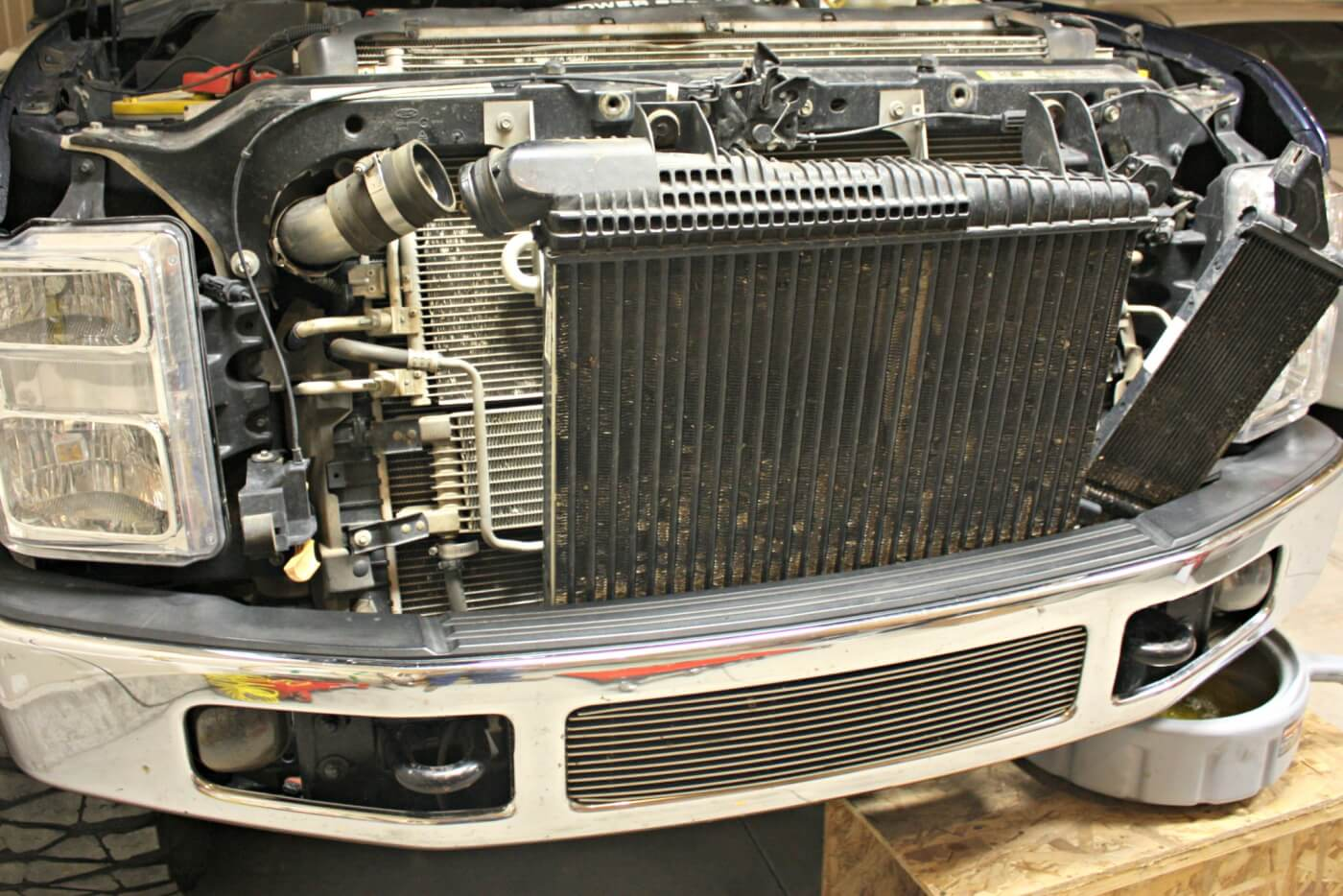 5. If there's a cooler attached to the driver's side of the intercooler, remove it as well. The intercooler can be lifted straight up out of its lower supports. With the intercooler removed, the transmission cooler and A/C condenser can be moved aside.