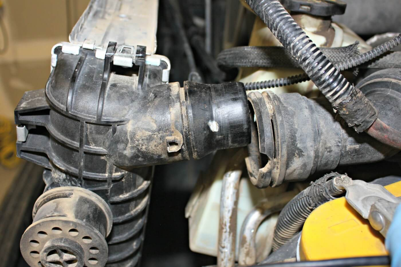 9. The factory coolant hoses can be disconnected from the radiator by simply sliding out the small metal U-clips with some pliers. Even though the radiator was drained, the lower radiator hose will still be full of coolant, so by disconnecting it from the radiator and not the engine, you should be able to avoid taking an antifreeze bath.