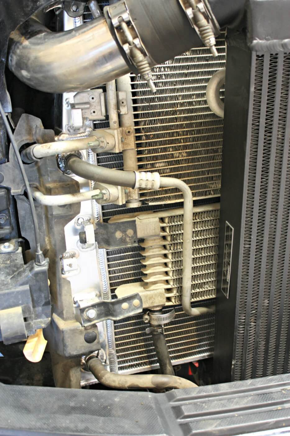 17. The new radiator comes equipped with mounting tabs and bolt holes that match the factory unit. Mishimoto supplies some new installation hardware, including the pieces needed to attach the A/C condenser.