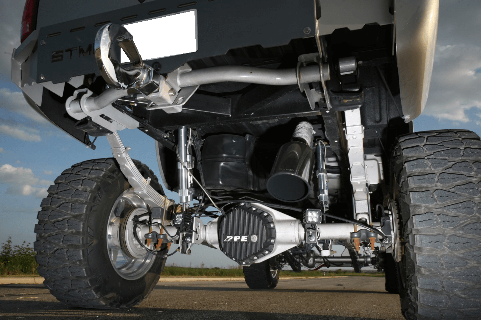 Arched 10-inch springs from Atlas combined with 2-inch blocks give the truck its 12-inch lift, and Fox shocks provide 14-inch of travel. A PPE rear differential cover dresses up the painted axle.