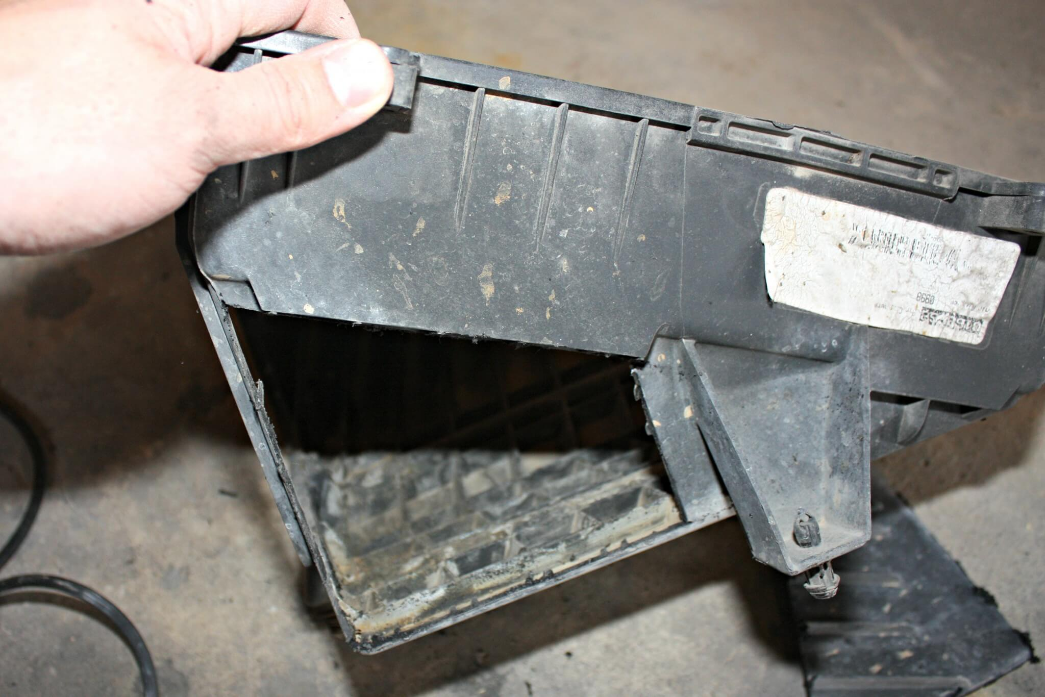 4. With the factory airbox removed from the truck, you'll notice a small opening on the passenger side of the box where it pulls air from the inner fender well area. On the front side of the airbox, you'll also notice a triangular-shaped section on the lower part of the box, seen here. This area can be cut out and removed to allow an additional spot for intake air to enter the box, adding some additional flow for the filter. Using a cutoff wheel, the plastic will cut easily. A small file can then be used to debur the edges before the box is reinstalled in the truck. While this may not seem like much, the added airflow can make an improvement over stock without costing you anything out of pocket.